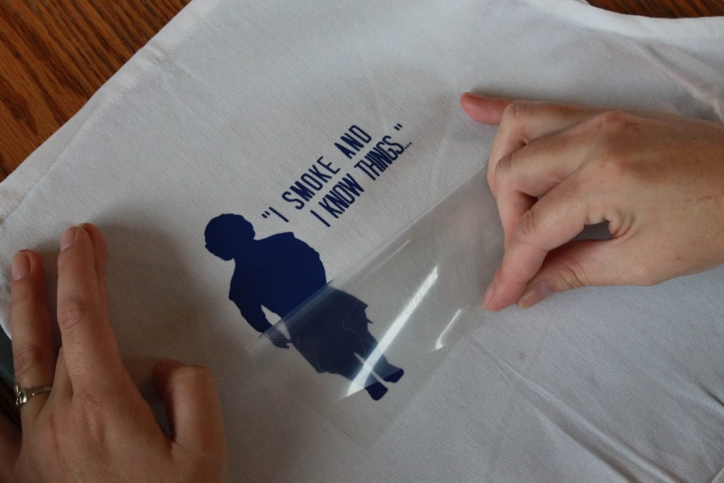 Hands peeling back transfer paper for Everyday Iron-on vinyl