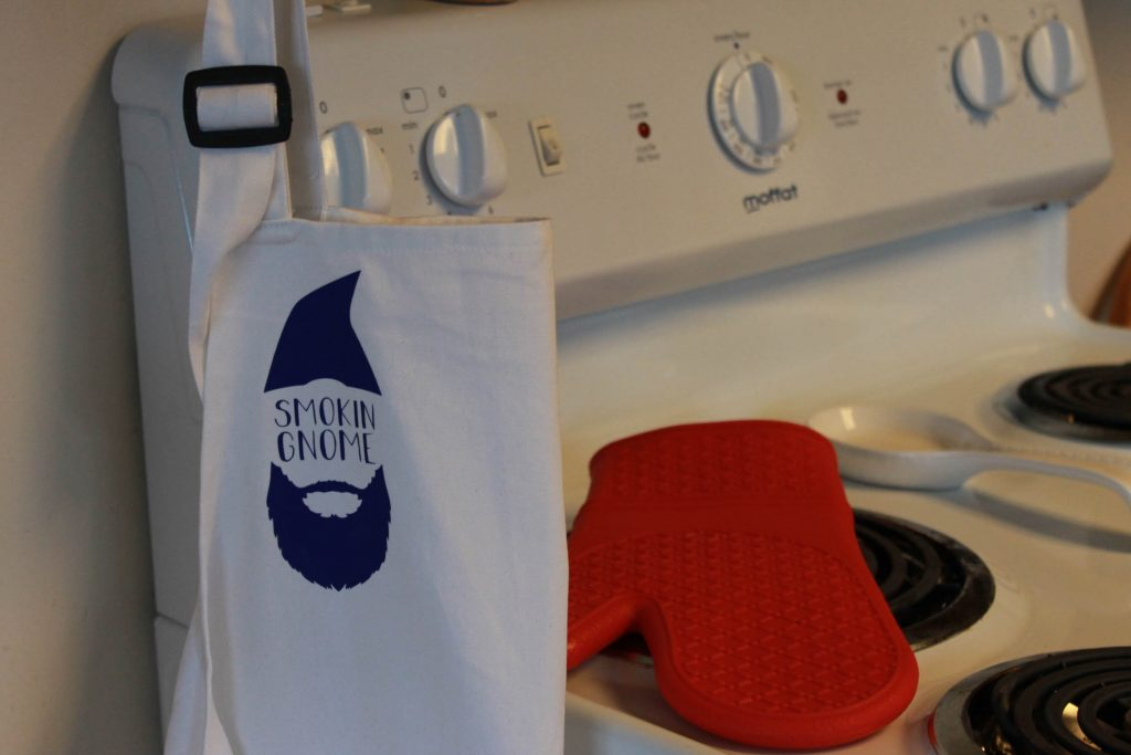 Smokin' Gnome EasyPress made apron hanging in kitchen next to stove