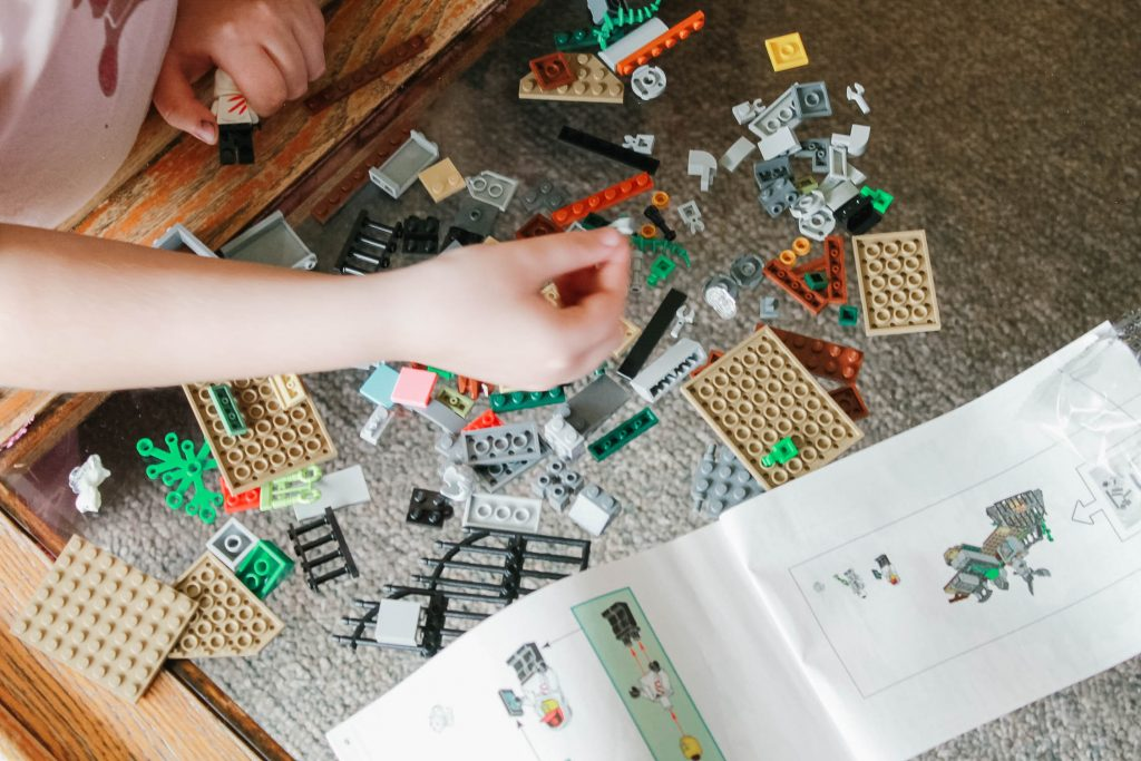 Childs hands putting together Lego pieces
