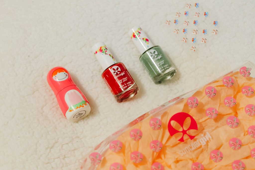 Suncoatgirl polishes on cotton background with lipbalm