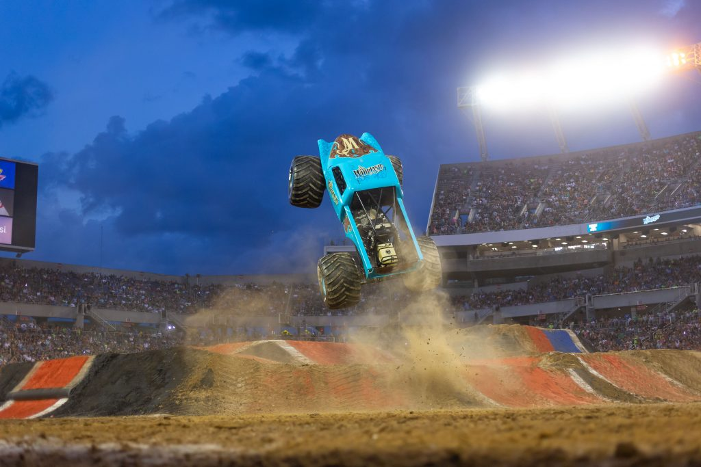 Monster Jam monster truck going over jump with clouds in background