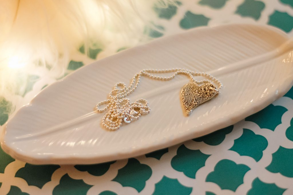 Flatlay of Smallprint tendertouch necklace on glass feather tray