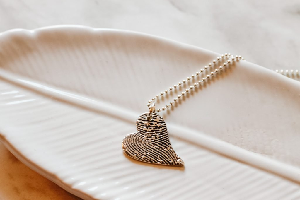 Close-up of Smallprint tendertouch necklace against white glass tray