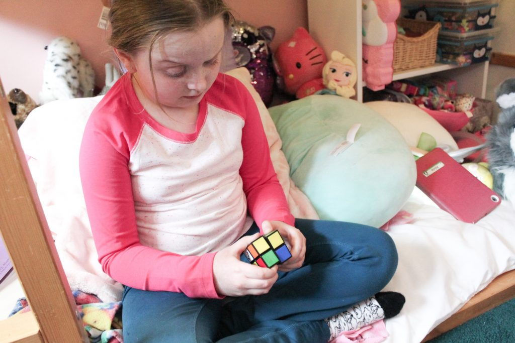 Child trying to solve Rubik's Cube