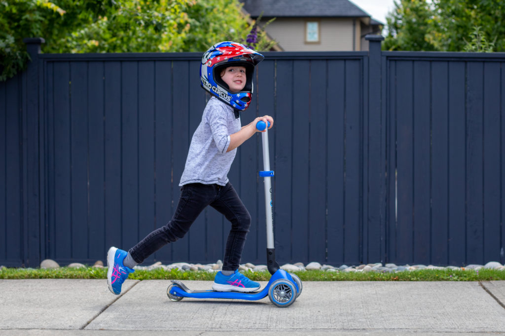 Child Riding Globber Scooter In Front Of Blue Fence With Motorcross helmet