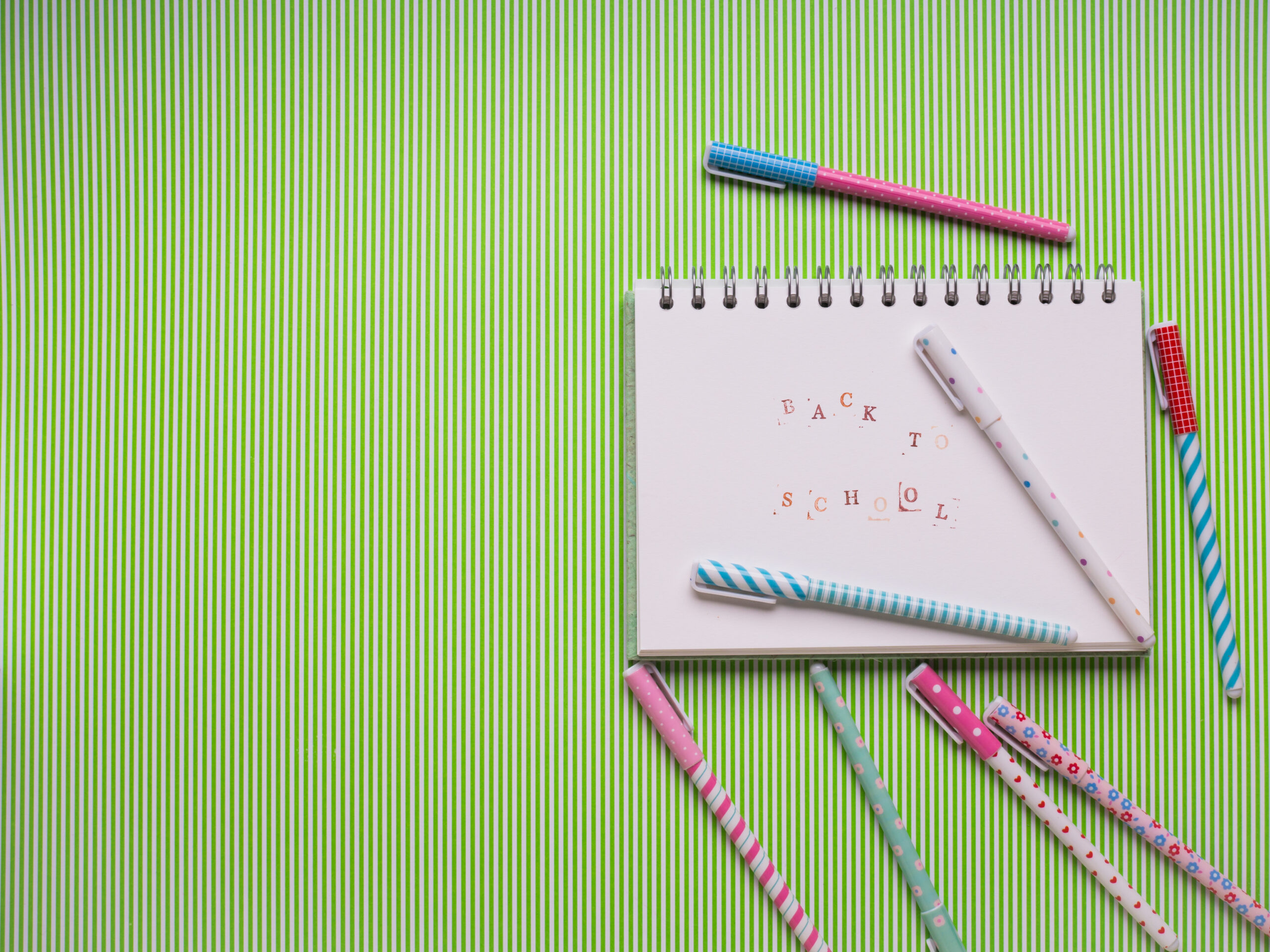 White notebook on a green table with pens scattered around