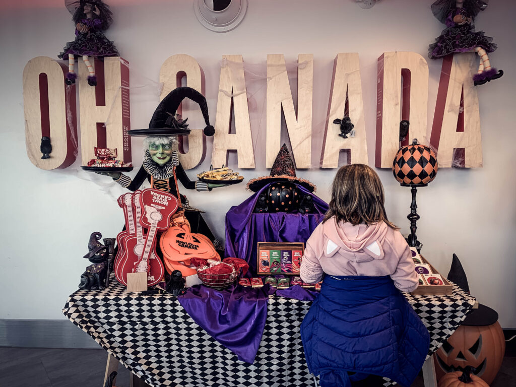 Girl standing in front of HowlOver Canada souvenir table with Oh Canada sign