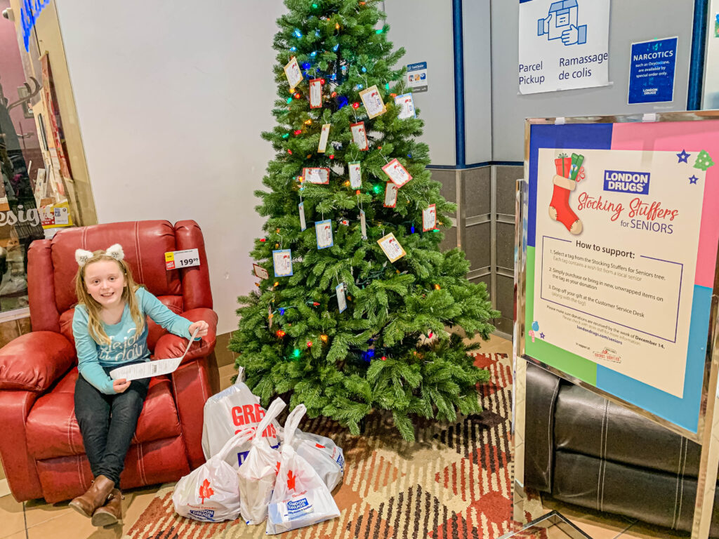 Child sitting in chair in front of Stocking Stuffers for Seniors tree at London Drugs