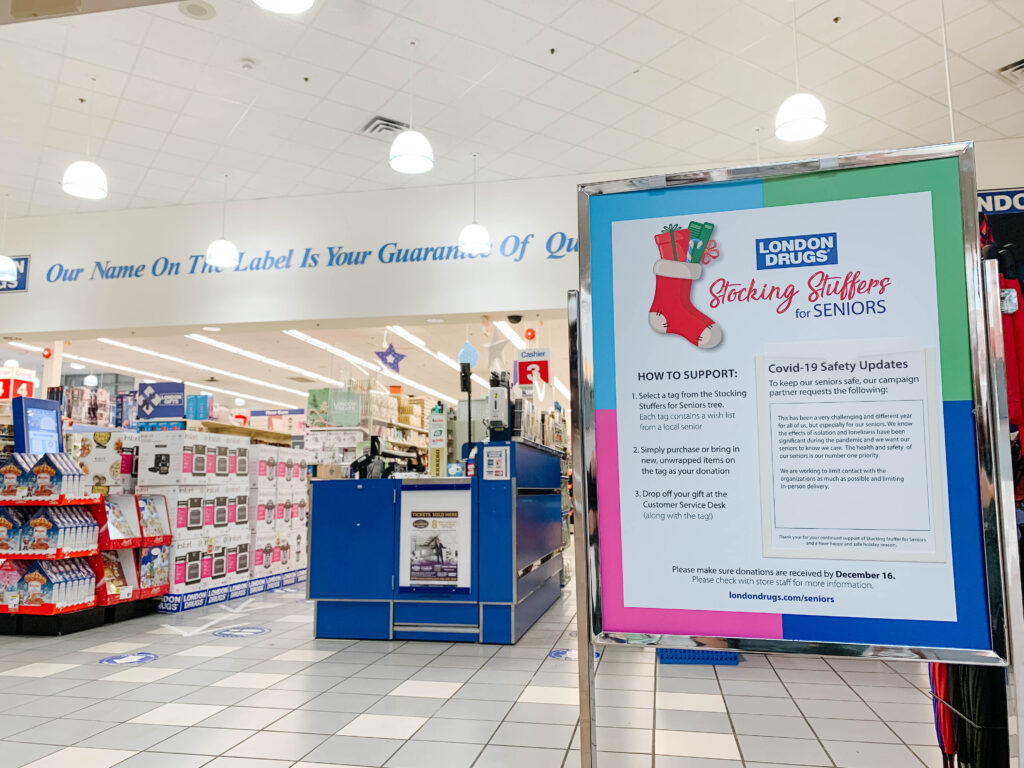 Image of inside London Drugs location with Stocking Stuffers for Seniors information board in front