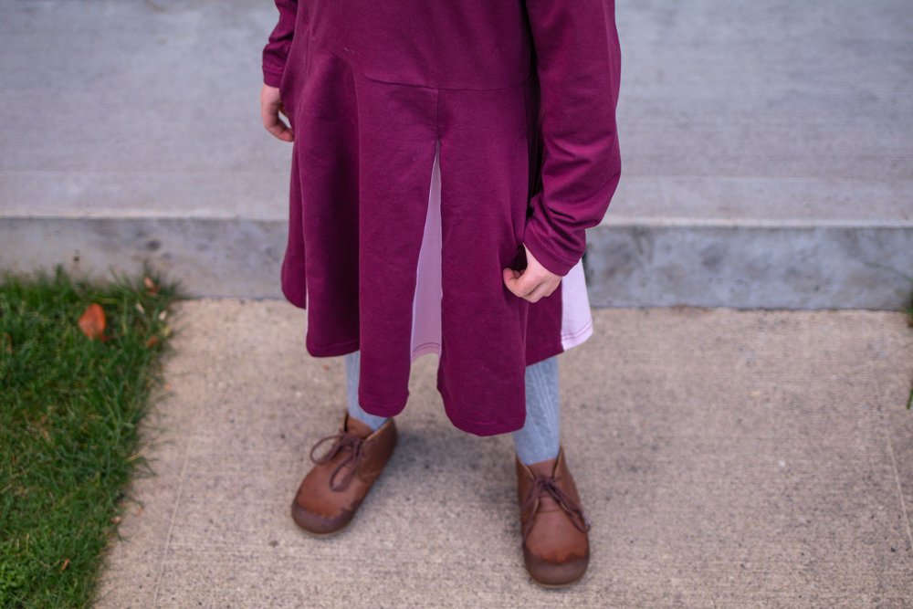 downward view of child wearing purple skater dress and brown boots