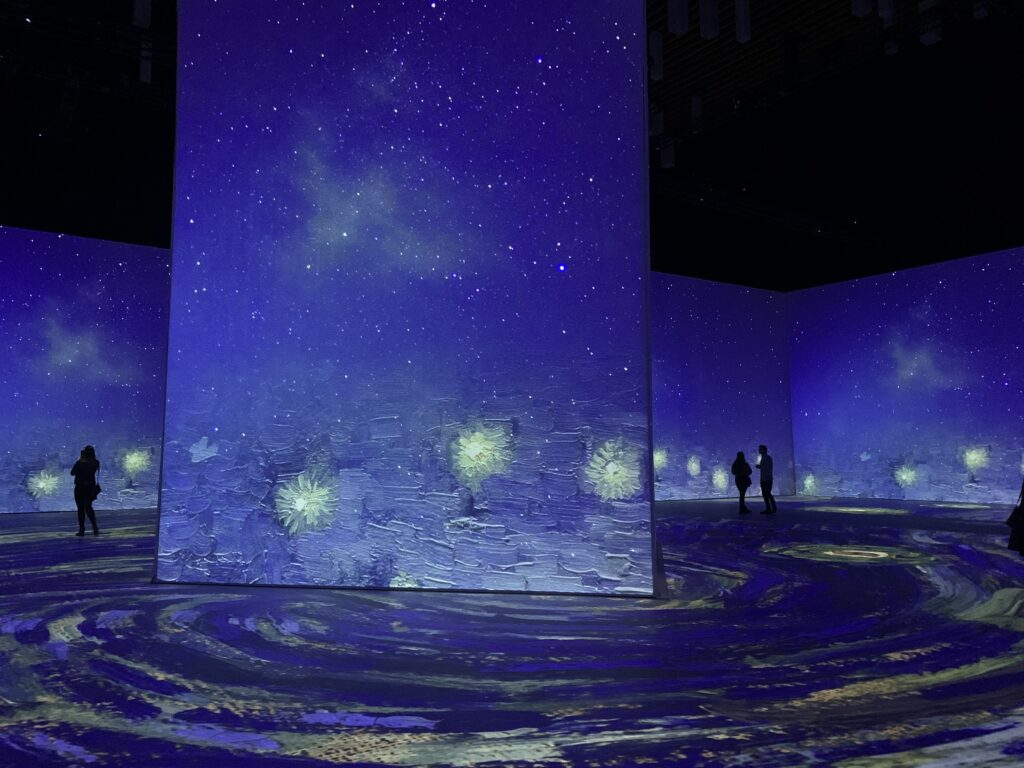 People silhouetted against Imagine Van Gogh projection screens